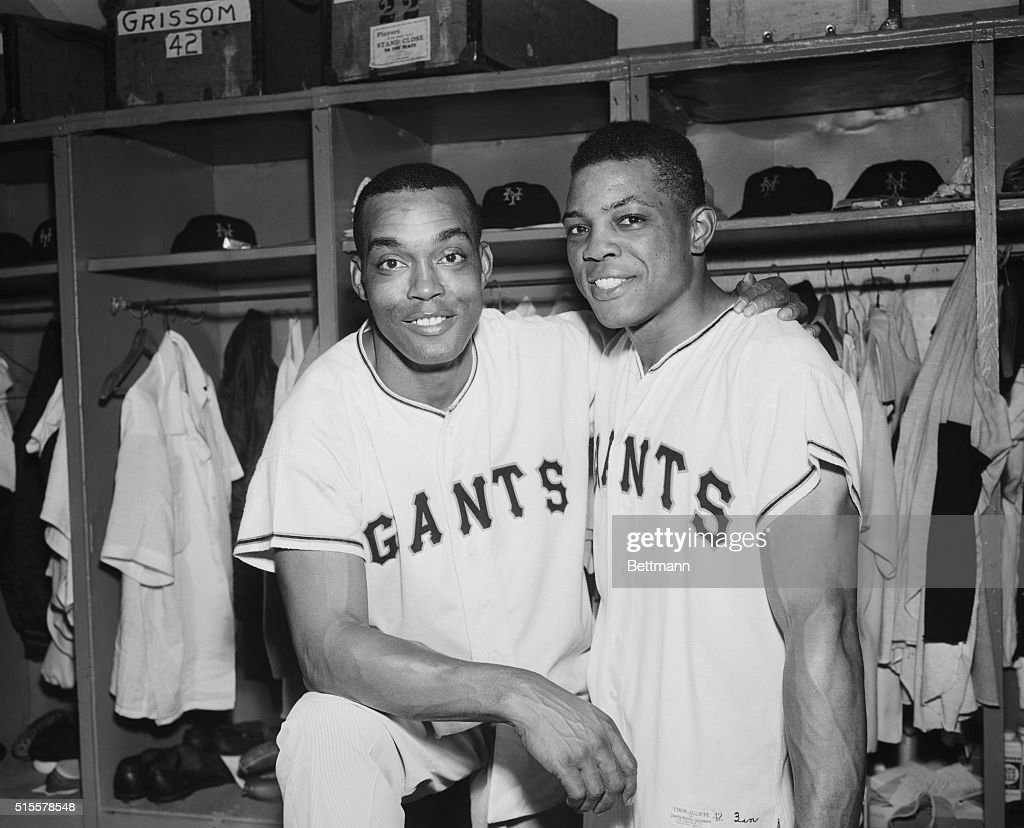 Two Giant stars, Monte Irvin (l), who singled with two out in the ninth inning of the June 22nd game to give New York a 3-2 win over Milwaukee and Willie Mays, whose second inning home run drove in whitey Lockman, congratulate each other in the dressing room after the game.
