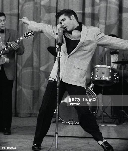 6/22/1956Hollywood CAHis arms stretched out and his head swaying rhythmically from side to side Elvis Presley loses himself as he pours out his song...