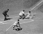 Pirates' outfielder Roberto Clemente is tagged out at the plate by Cub catcher Harry Chiti on Frank Thomas' hit to left field in the first inning of...