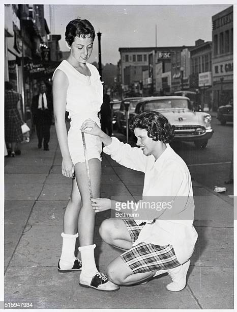 6/28/56White Plains New York Sally Leech puts the tape measure to the leg of Marilyn Veasey on Main Street in White Plains to see how she stands in...