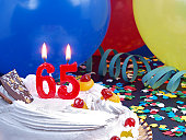 65th. Anniversary / Birthday cake in a Party background with balloons and party strings.