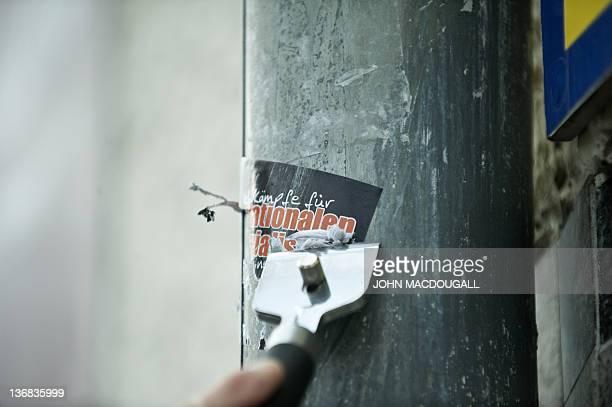 COLE 66yearold antiNazi activist Irmela MensahSchramm scrapes a Nazi sticker off a drainpipe in eastern Berlin's Lichtenberg district December 20...