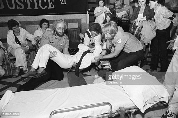 6/7/1982Springfield IL Sonia Johnson ERA faster is lifted onto a stretcher by medical technicians at the Illinois State capitol after complaining of...