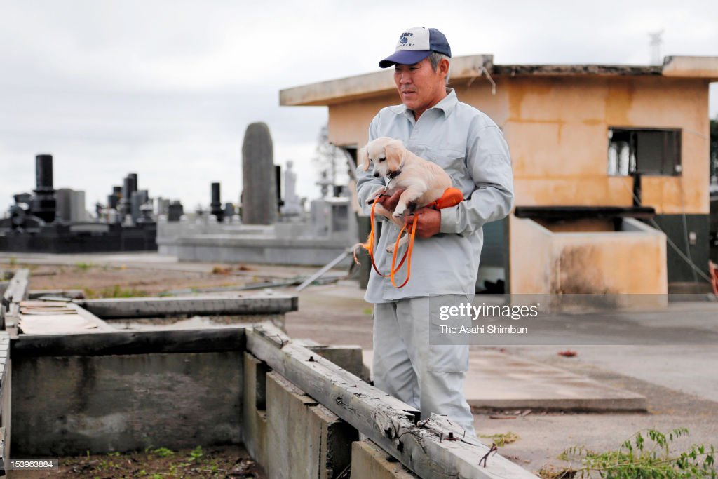 69-year-old Manabu Aihara, holding his dog Hana, stands at his house used to be, on October 11, 2012 in Minamisoma, Fukushima, Japan. He lost his wife and a daughter and visits almost everyday to the place where he built his 'My Home' 40 years ago. Japan marks 19 months anniversary of the earthquake and following tsunami, which caused more than 20,000 casualties.