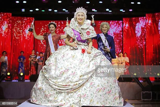 69yearold woman Han Bin holds her trophy after being crowned 'Miss Tourism International ' during Miss Tourism International 2016 China Final on...