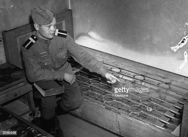 A russian soldier sitting on the bed in the cellars of Hitler's Chancellery where he and Eva Braun are alleged to have poisoned themselves