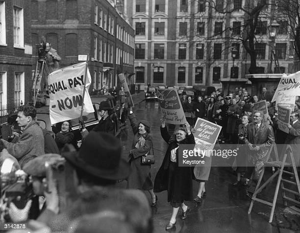 Demonstrators in Smith Square London demand equal pay from R A Butler the Chancellor of the Exchequer who is leaving Conservative Party headquarters...