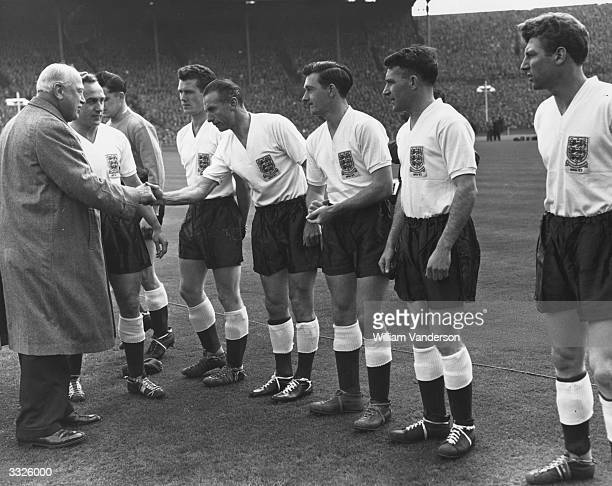 Lord Roseberry shaking hands with Stanley Matthews of the England team when being introduced to them on the occasion of an England v Scotland match...