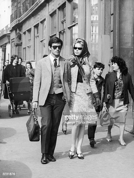 French actors Sami Frey and Brigitte Bardot are followed by fans as they walk on Boulevard RichardLenoir Paris France Both wear dark sunglasses...