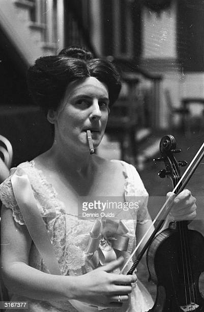 Joyce Nixon who plays a band member in the opera 'Victory' smokes a cigar during a break from rehearsals at the Royal Opera House