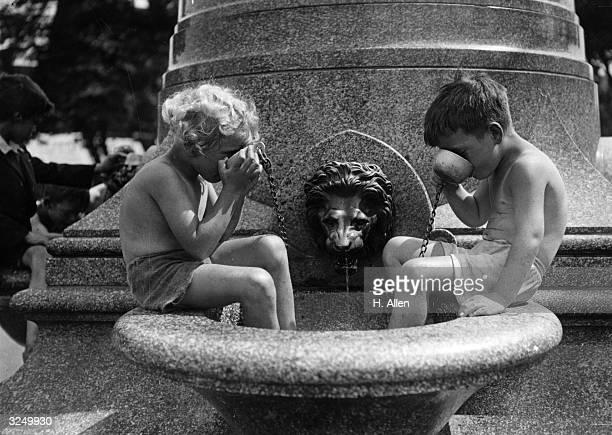 Children enjoy a cooling drink from the fountain on Clapham Common