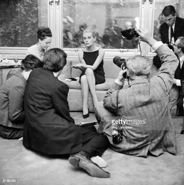Photographers surrounding the French actress Jeanne Moreau after it was announced she is to marry designer Pierre Cardin