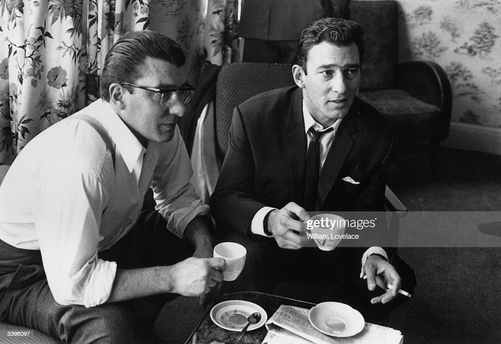 London gangsters Ronnie and Reggie Kray having a cup of tea at home. They had just spent 36 hours being questioned by the police about the murder of George Cornell.