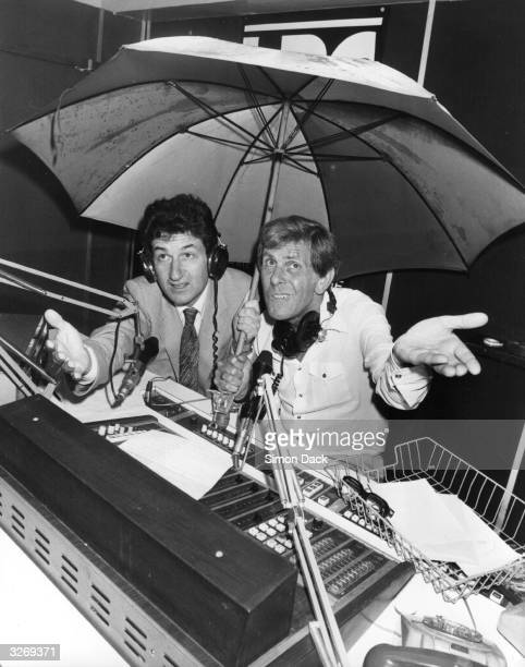 Radio presenters Bob Holness and Douglas Cameron of LBC radio are sheltering under an umbrella as rainwater pours into their studio during a...