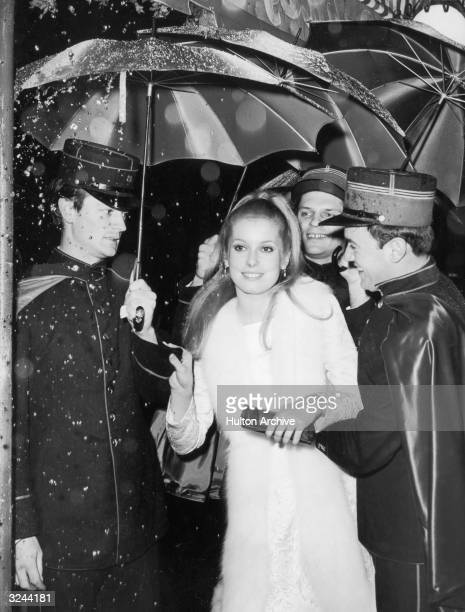 French actor Catherine Deneuve is ushered by gendarmes holding colorful umbrellas to shield her from rain falling from a mechanical device as she...