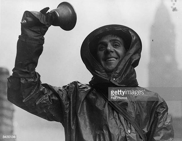 An air raid warden ringing a bell to signal the 'All Clear' after a gas raid