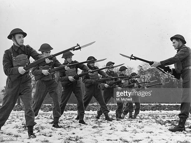 A Home Guard squad learning bayonet fighting in the snow at Stanborough's Hydro Annexe Garston Watford Hertfordshire