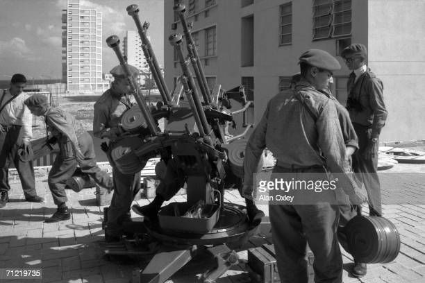 Cuban militiamen set up an antiaircraft gun on a gas station roof on Havana's Malecon Drive as Fidel Castro warns that the US will launch an invasion...