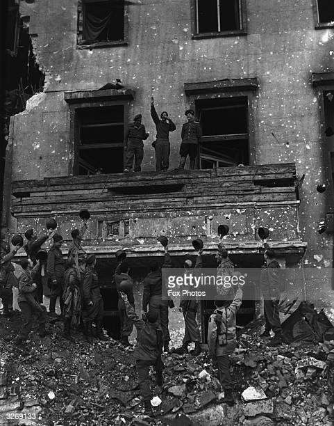 American Corporal Russell M Ochwad impersonates Hitler on the balcony of the bombed out Chancellory saluting some troops below
