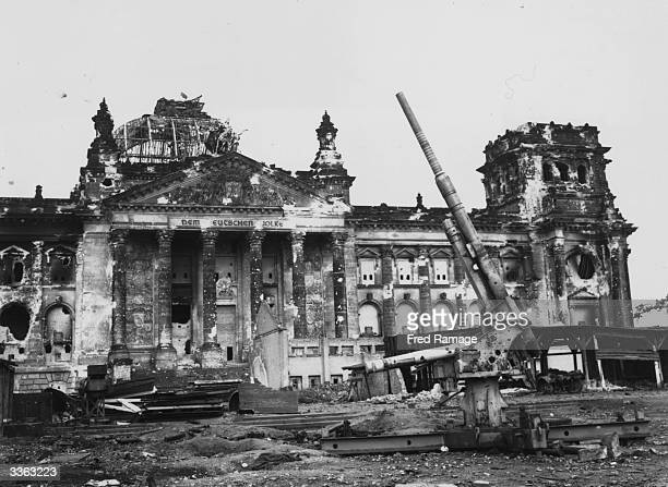 Artillery in front of the bombdamaged Reichstag the former seat of the German parliament in Berlin at the end of the Second World War