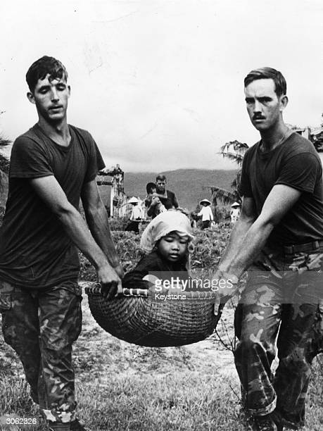 Two American marines carrying a young Vietnamese refugee in a basket during the evacuation of a village near Da Nang