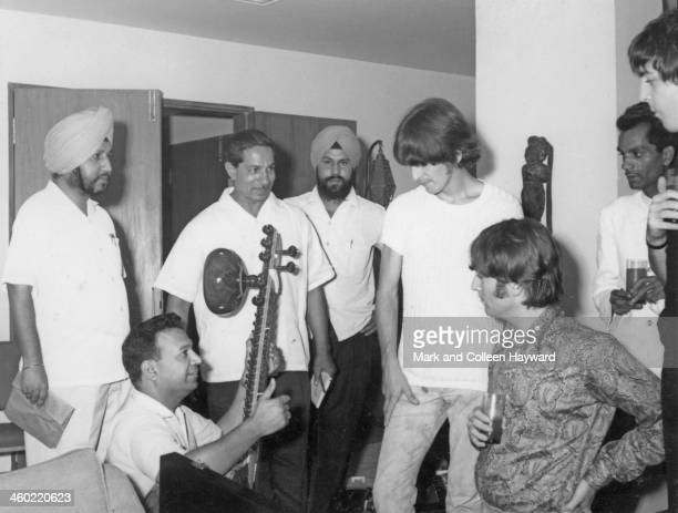 George Harrison John Lennon and Paul McCartney from The Beatles are given a sitar demonstration in Rikhi Ram's instrument shop in New Delhi India on...