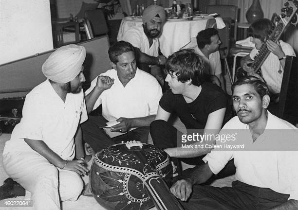 Paul McCartney and George Harrison behind from The Beatles are given a sitar demonstration in Rikhi Ram's instrument shop in New Delhi India on 6th...