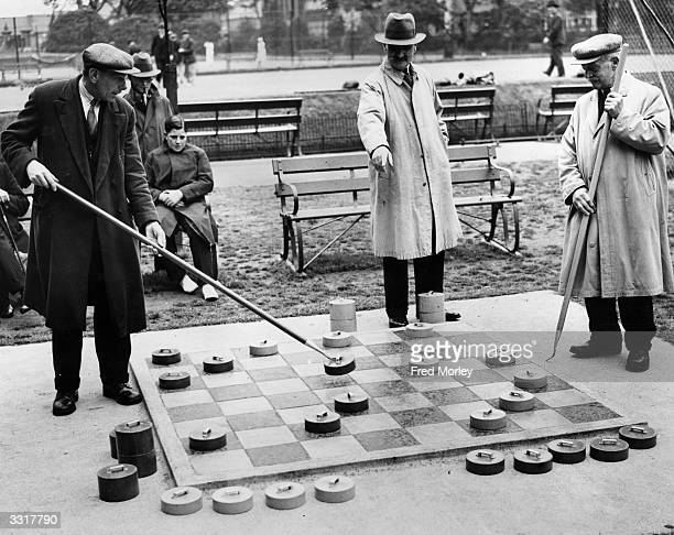 Players position their pieces during a game of draughts on a large outdoor draught board set up in a London park