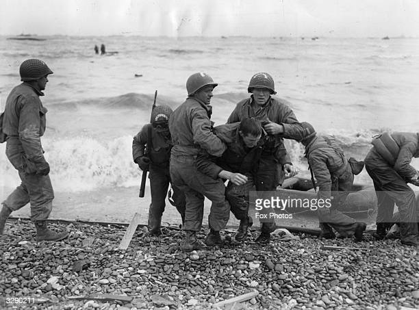 American troops helping their injured friends from a dinghy after the landing ship they were on was hit by enemy fire during the Allied invasion of...
