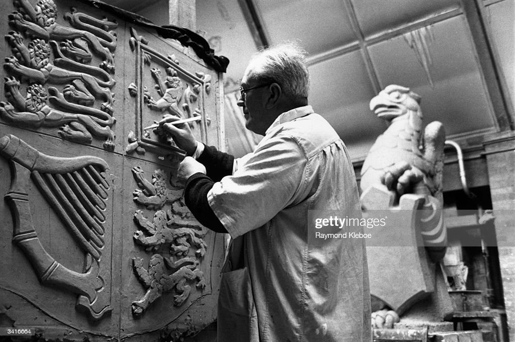 A man carving the Royal Crest which will join figures of the Queen's Beasts which will stand at the entrance to the newly-built Coronation annexe of Westminster Abbey. Original Publication: Picture Post - 6536 - About The Queen's Beasts - pub. 1953