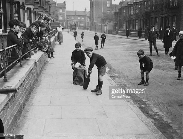 Young boys playing cricket in a London street