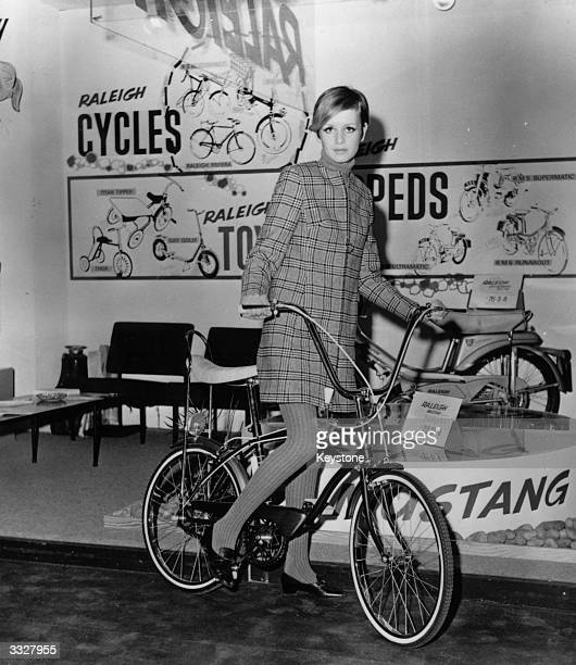 Fashion model Twiggy posing on a bike at the Daily Mail Ideal Home Exhibition