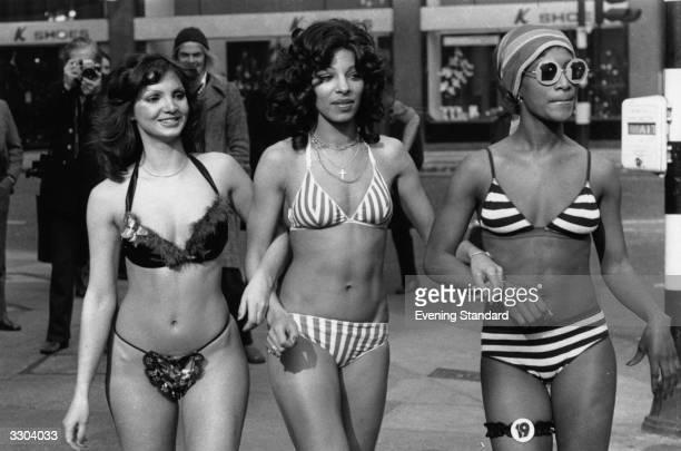 Three women model bikinis in a London high street
