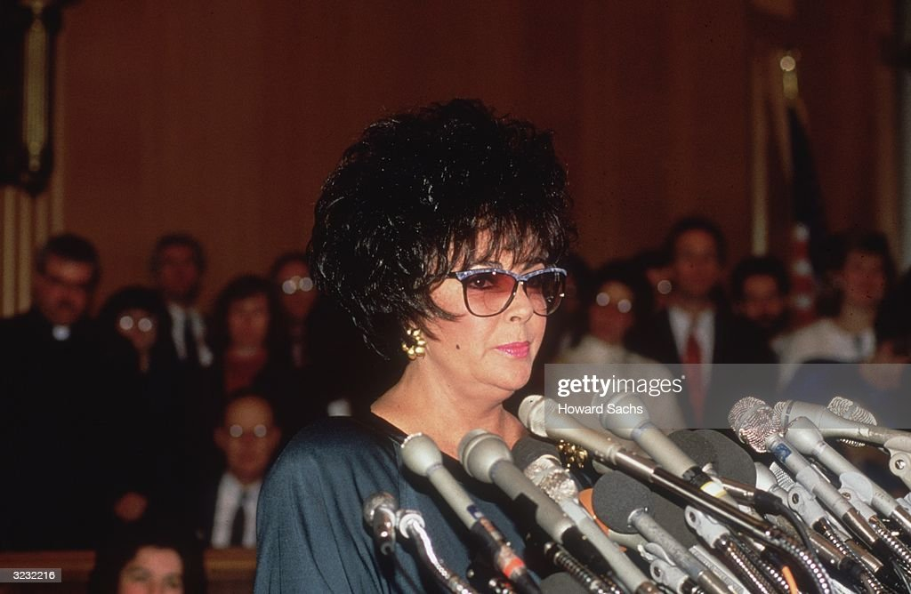 British-born actor Elizabeth Taylor wearing sunglasses and standing at microphones at a press conference for AIDS legislation, Washington, D.C..