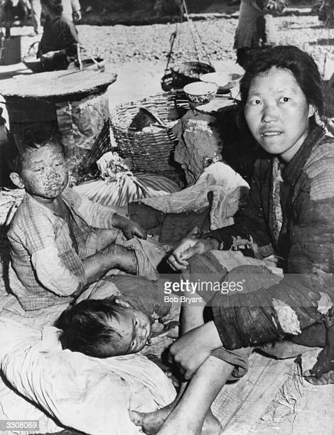 A refugee family from one of China's famine areas lying by the side of the road during the civil war Both of the small children are suffering from...
