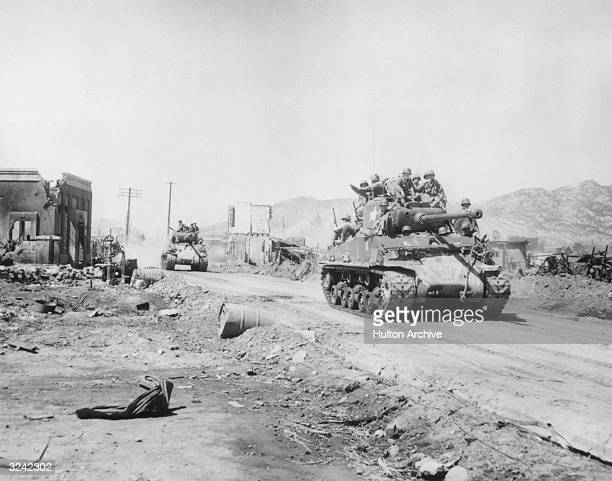 United Nations soldiers sit on top of two UN tanks rumbling through the wartorn main street of Uijongbu after a patrol searching for enemy forces...