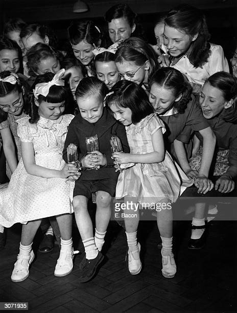 Children in Wilmot School Bethnal Green London clutching packets of coronation pencils which are souvenirs donated by the LCC