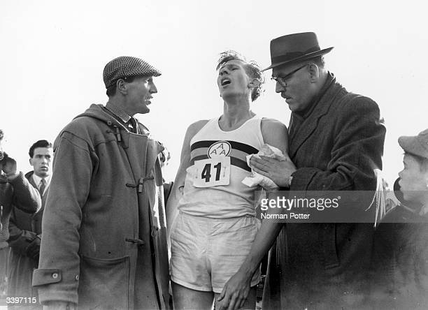 Roger Bannister gasps for breath at the end of his record breaking mile run at Iffley Road Oxford He was the first person to run the mile in under...
