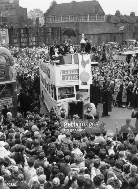 The players of Tottenham Hotspur proudly display their trophy to the crowd from an open top bus during a civic reception North London in honour of...