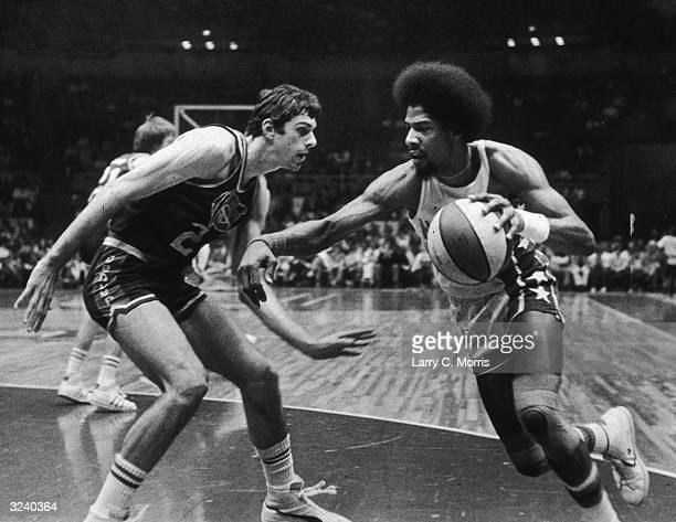 American basketball player Julius Erving of the New Jersey Nets nicknamed 'Dr J' driving past Bobby Jones of the Denver Nuggets during a game