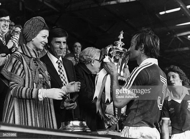 Mick Mills the captain of Ipswich town kissing the FA Cup after his team's victory over Arsenal Watching him are Princess Alexandra and the secretary...