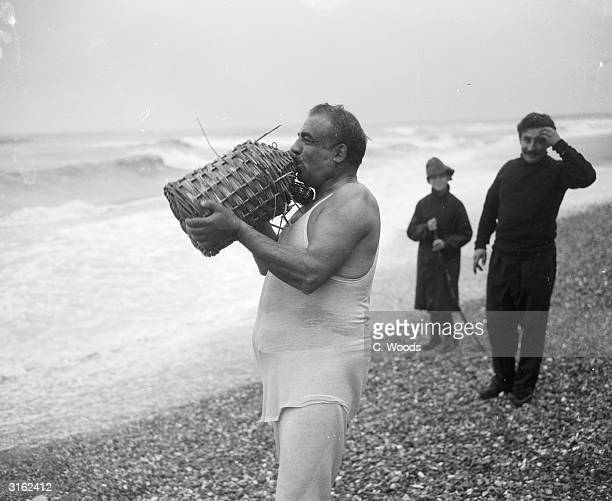 Captain Athanasis Conmandareas takes a swig from a wicker container after his schooner La Morna was wrecked off the Isle of Wight