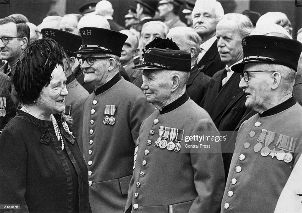 Elizabeth, the Queen Mother (1900 - 2002) chats to a line of Chelsea pensioners after planting a poppy in the Field of Remembrance outside Westminster Abbey, London.