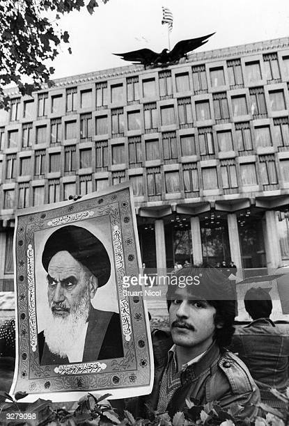An Iranian student holds up a picture of the Ayatollah Khomeini outside the American embassy in London to demonstrate for Shah's extradition from the...