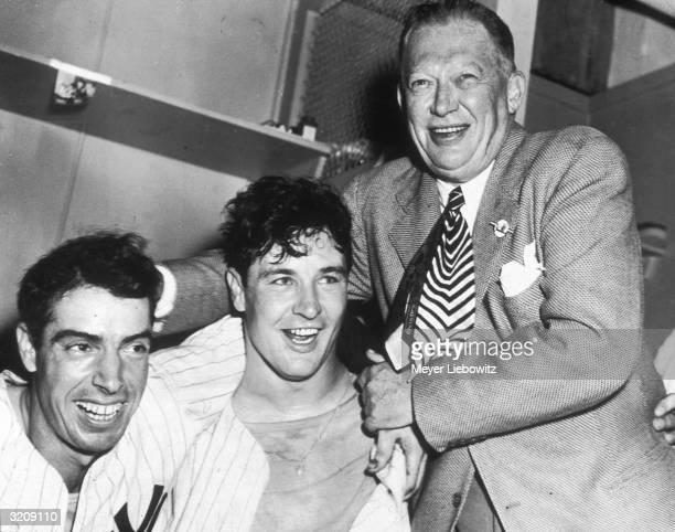 Larry MacPhail wraps his arms around New York Yankees Joe DiMaggio and Joe Page after the Yankees won the World Series by defeating the Brooklyn...