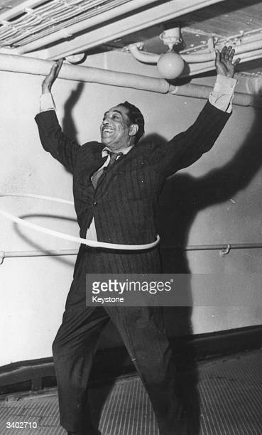 American big band leader and legendary jazz pianist Duke Ellington composer of between 2000 / 5000 tunes shows how he can hulahoop on the deck of SS...