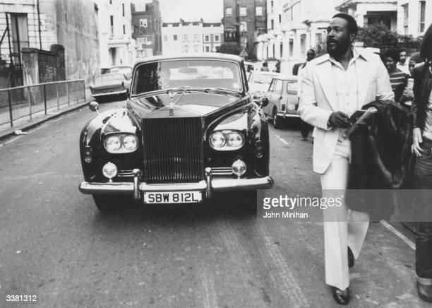 American soul singer Marvin Gaye walking ahead of his Rolls Royce in Notting Hill London