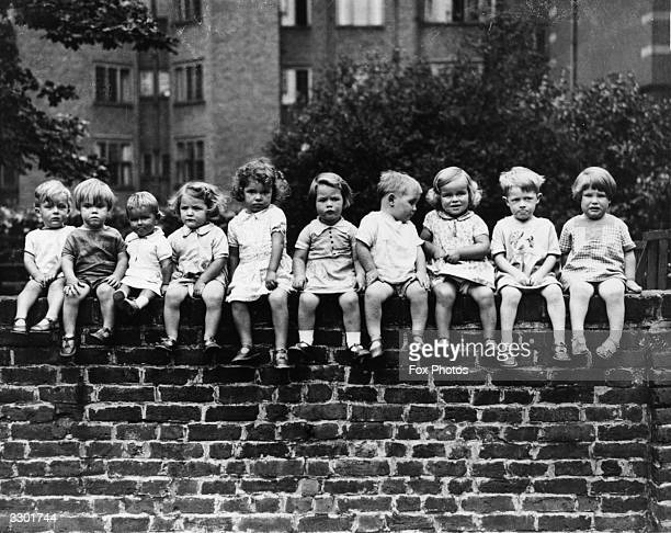 Ten young children whose mothers work as domestic servants sitting on a wall at Denvers Street Chelsea London where helpers look after them during...