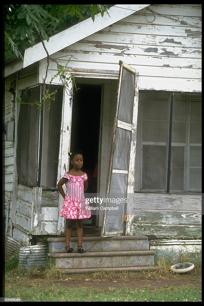 6-yr-old Danielle McNeil on porch of family home, in need of paint job & other repairs, living in town named by Census figures as poorest place in US.