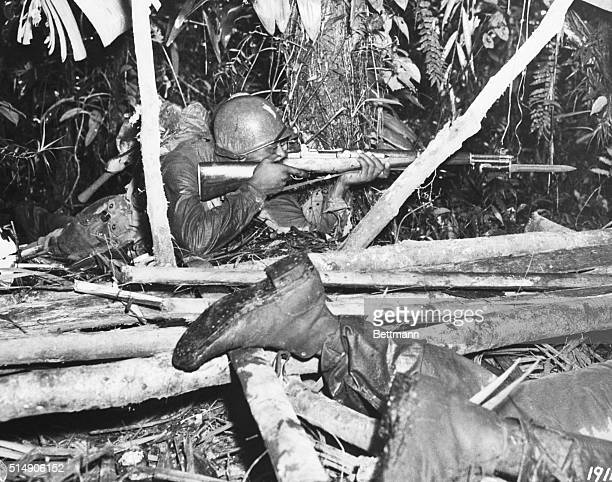 7/14/1944South Pacific One of the Negro soldiers of the American 93rd Division fires from a prone position just outside a Jap leanto while on patrol...